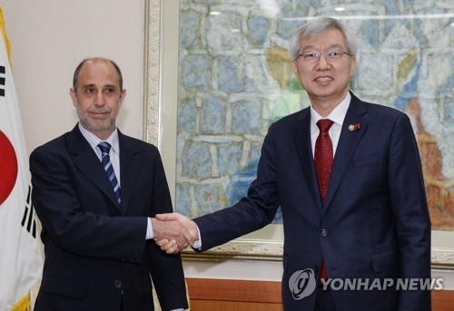 1月7日上午,在韩国外交部,李泰镐(右)与金塔纳握手。(韩联社)