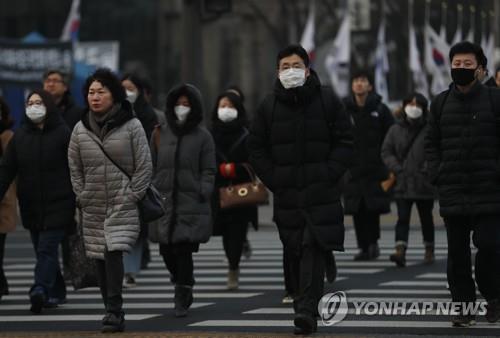 在街头上,市民佩戴口罩出行。(韩联社)