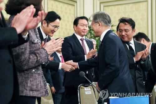 1月15日,在青瓦台,韩国总统文在寅(前排左一)出席韩国大中型企业代表座谈并同与会企业家握手。(韩联社)
