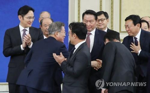 1月15日,在青瓦台,韩国总统文在寅(前排右)出席韩国大中型企业代表座谈并同与会企业家握手。(韩联社)