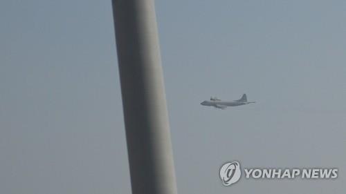 """资料图片:1月23日下午,日本P-3巡逻机从约60米的高度贴近韩国""""大祚荣""""号驱逐舰右弦飞行,距舰桥天线仅有1公里远。(韩联社/韩国防部供图)"""
