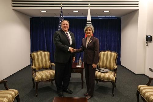 当地时间2月14日,在波兰华沙,韩国外长康京和(右)和美国国务卿蓬佩奥举行会晤前握手合影。(韩联社/外交部供图)