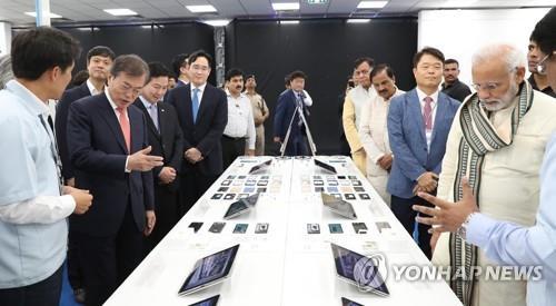 资料图片:2018年7月9日,在三星电子诺伊达第2工厂,韩国总统文在寅(左排前二)和印度总理莫迪(右排前一)在三星电子副会长李在镕(左排前四)的陪同下参观三星电子产品。(韩联社)
