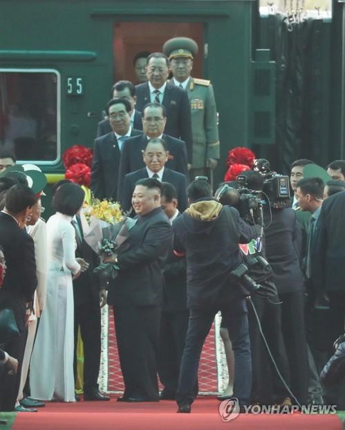 2月26日,金正恩抵达越南谅山省同登站后,从越方人员的手中接过花束。(韩联社)