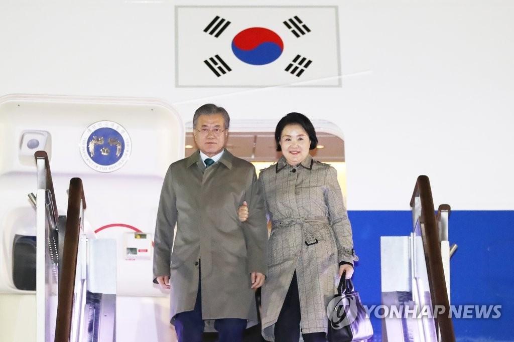 3月16日晚,在位于京畿道城南市的首尔机场,结束东盟三国之旅返回的文在寅(左)和夫人金正淑女士走出专机。(韩联社)