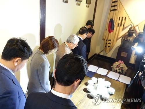 代表团向金九先生半身像默哀。(韩联社)