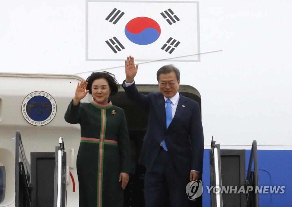 资料图片:当地时间4月11日下午,在华盛顿杜勒斯国际机场,韩国总统文在寅(右)和第一夫人金正淑向欢送人群挥手致意。(韩联社)