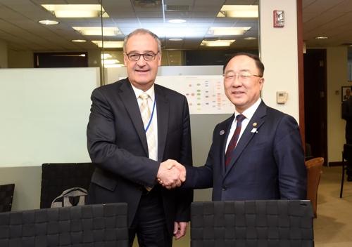 当地时间4月13日,在华盛顿,韩国经济副总理兼企划财政部长官洪楠基(右)与瑞士经济部长帕尔莫兰握手。(韩联社/企划财政部供图)