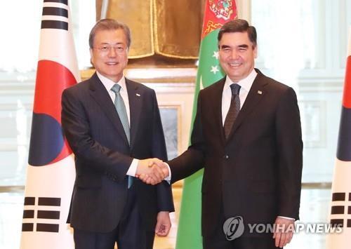 资料图片:当地时间4月17日,在阿什哈巴德,文在寅(左)同土库曼斯坦总统库尔班古力·别尔德穆哈梅多夫亲切握手。(韩联社)