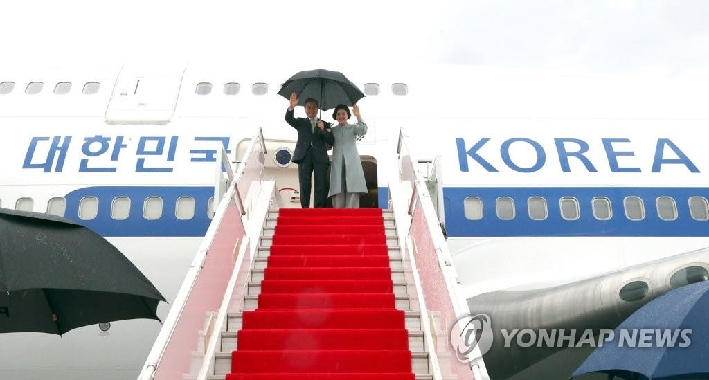 资料图片:当地时间4月18日,文在寅(左)和夫人金正淑女士飞抵乌兹别克斯坦。(韩联社)
