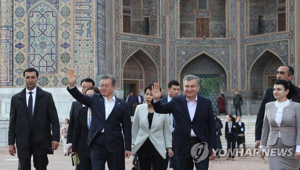 当地时间4月20日下午,在位于撒马尔罕市中心的雷吉斯坦广场,正在对乌兹别克斯坦进行国事访问的韩国总统文在寅(左)同乌兹别克斯坦总统沙夫卡特·米尔济约耶夫向欢迎人群挥手致意。(韩联社)