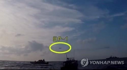 资料图片:这是韩国国防部1月4日在视频网站优兔发布的日机抵近韩舰的视频截图。用黄圈标出的是日本巡逻机。(韩联社)