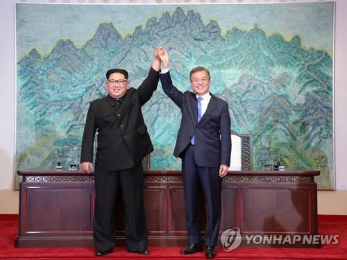 资料图片:2018年4月27日,在板门店,韩国总统文在寅(右)和朝鲜国务委员会委员长金正恩举行会谈。(韩联社)
