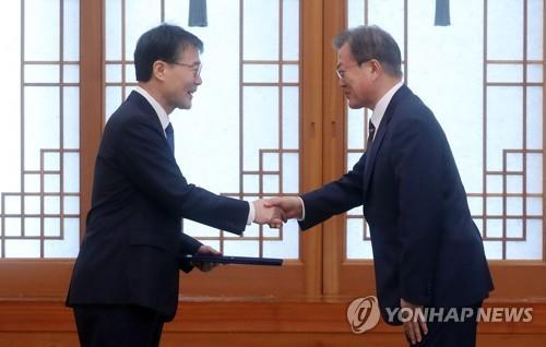 文在寅(右)与张夏成握手。(韩联社)