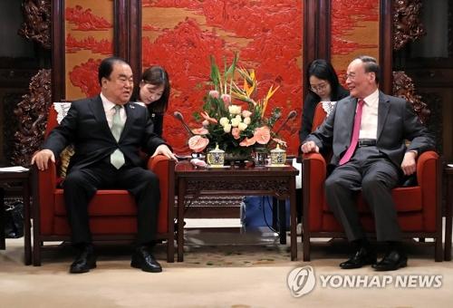 当地时间5月8日,在北京,文喜相(左)和王岐山亲切交谈。(韩联社/国会发言人室供图)