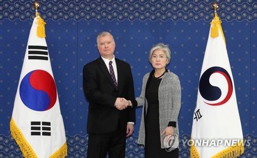 5月10日,在首尔外交部大楼,韩国外交部长官康京和(右)同美国国务院对朝政策特别代表比根握手合影。(韩联社)