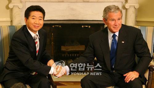 资料图片:2006年9月15日,在美国白宫,韩国总统卢武铉(左)与美国总统小布什在会谈上握手合影。(韩联社)