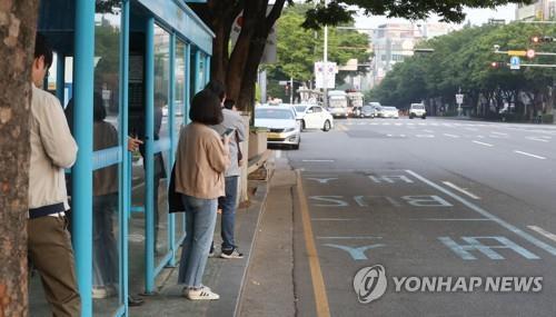 资料图片:5月15日上午,在蔚山市南区的一处公交站,市民焦急地等待公交车。(韩联社)