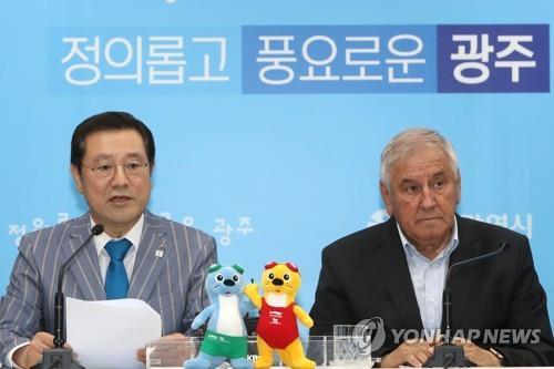 5月23日,国际泳联(FINA)执行主任马库莱斯库(右)与光州市长李庸燮联合召开记者会。(韩联社)