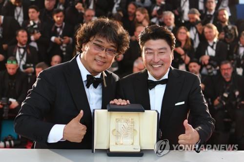 奉俊昊(左)和主演宋康昊领奖后手捧奖杯合影。韩联社/欧新社