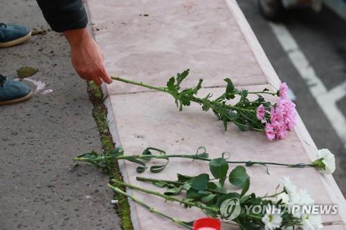 人们摆放鲜花哀悼沉船遇难者。(韩联社)