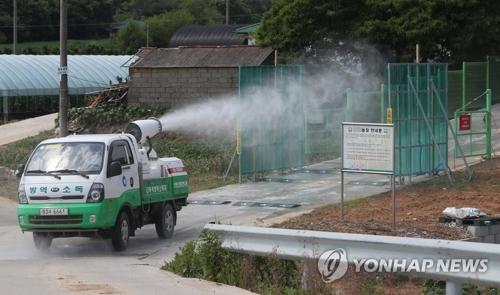 资料图片:6月3日上午,在靠近朝鲜的仁川市江华郡一家养猪场,一辆防疫车辆正在进行防疫消毒。(韩联社)