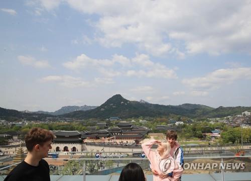 资料图片:外国游客在首尔景区拍照留念。 韩联社