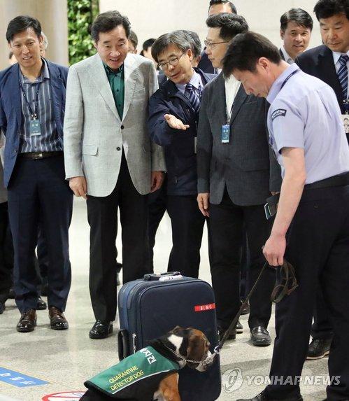 资料图片:5月18日,国务总理李洛渊(左二)在仁川机场视察非洲猪瘟防控检疫工作。 韩联社