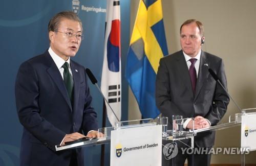 6月15日,在瑞典萨尔特舍巴登大酒店,韩国总统文在寅(左)和瑞典首相勒文共同会见记者介绍会谈结果。 韩联社