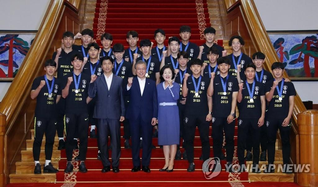 6月19日下午,在青瓦台,文在寅(前排左四)与第一夫人金正淑同韩国20岁以下(U20)足球队合影留念。韩联社