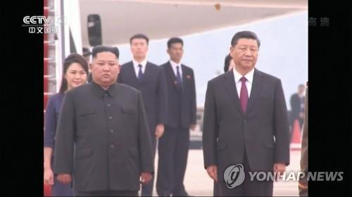 6月20日,金正恩(左)和习近平在平壤顺安机场检阅朝鲜人民军仪仗队。 韩联社/中国央视截图(图片严禁转载复制)