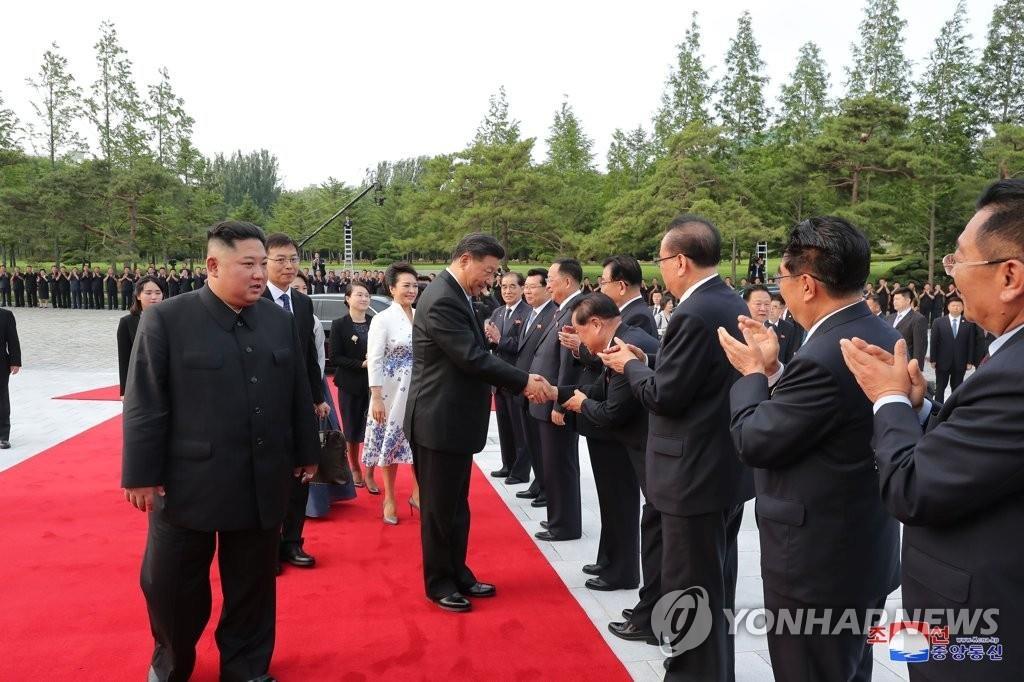 在金正恩的介绍下,习近平与劳动党政治局委员们一一握手。 韩联社/朝中社(图片仅限韩国国内使用,严禁转载复制)