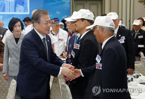 6月24日,文在寅(左)同韩战有功人员亲切握手。 韩联社