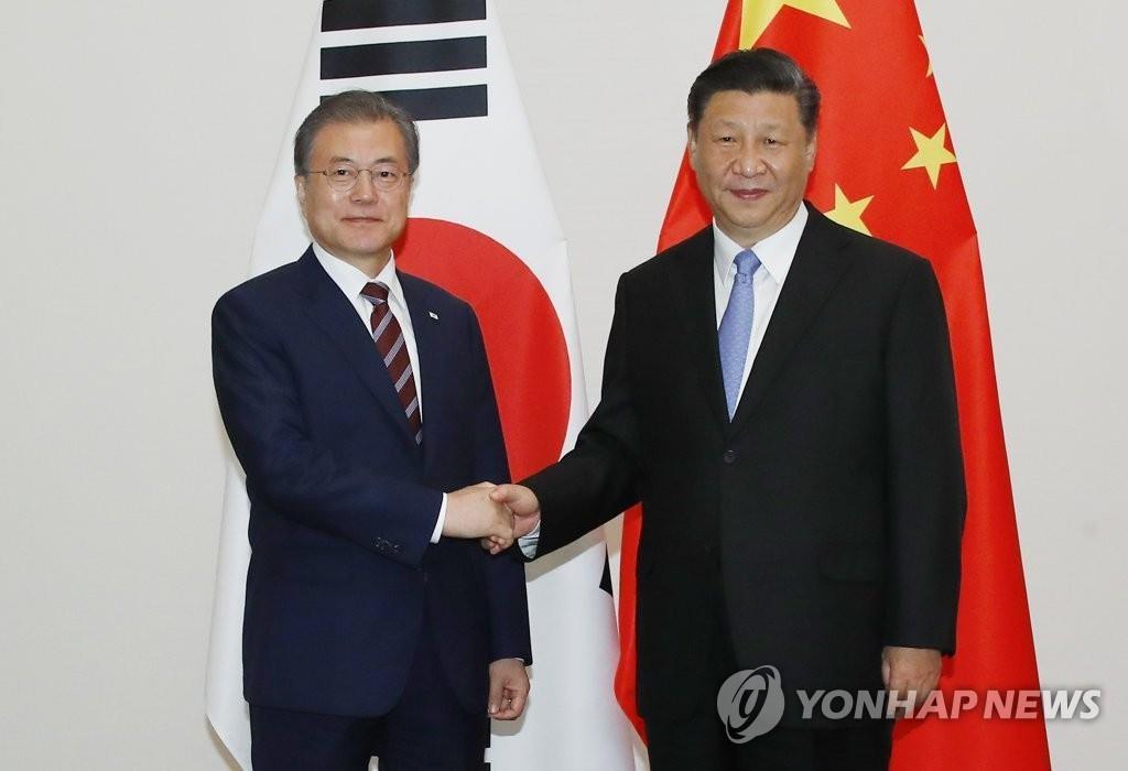 6月27日,在日本大阪,韩国总统文在寅(左)同中国国家主席习近平握手合影。 韩联社