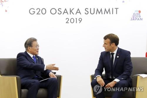 文在寅(左)与马克龙会谈。 韩联社