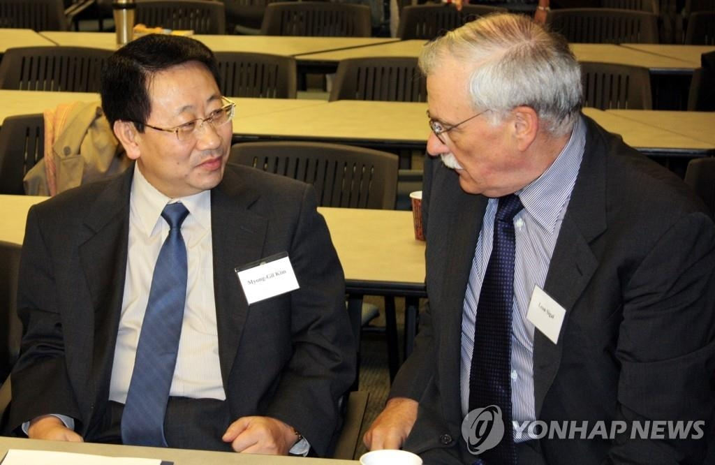 资料图片:2009年2月26日,在美国,时任朝鲜常驻联合国代表部公使金明吉(左)出席有关朝核问题六方会谈的学术会议,并与美国社会科学研究理事会东北亚地区安全合作项目主任里昂·西格尔进行交谈。 韩联社