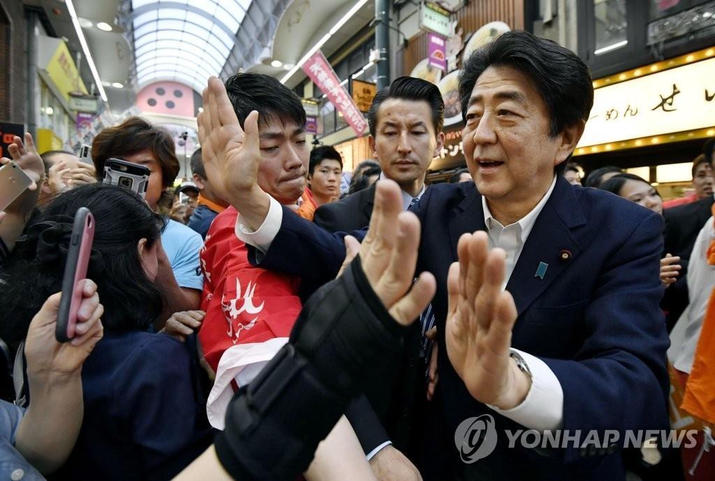 资料图片:7月6日,在大阪,日本首相安倍晋三(右)与选民击掌致意。 韩联社/共同社(图片严禁转载复制)