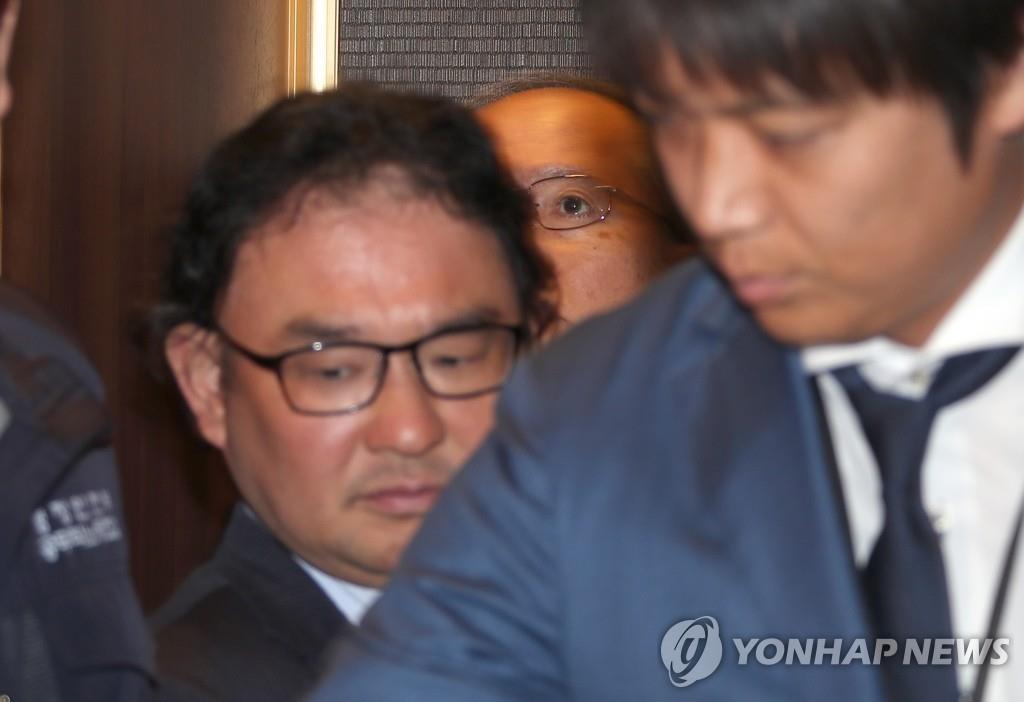 资料图片:7月1日,在首尔市韩国外交部,日本驻韩大使长岭安政(最里面)为躲避记者从地下四层停车场乘电梯上楼。 韩联社