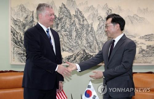 资料图片:李度勋(右)与比根 韩联社