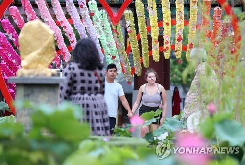 资料图片:7月10日,在位于首尔钟路区的曹溪寺,外国游客欣赏莲花。 韩联社