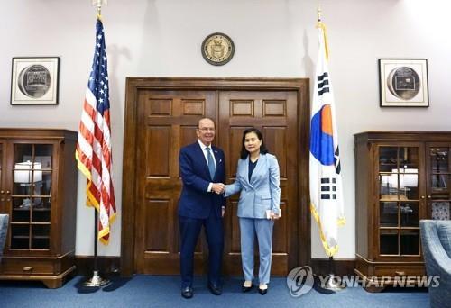 资料图片:当地时间7月25日,在华盛顿,韩国产业通商资源部通商交涉本部长俞明希(右)同美国商务部长罗斯合影。 韩联社