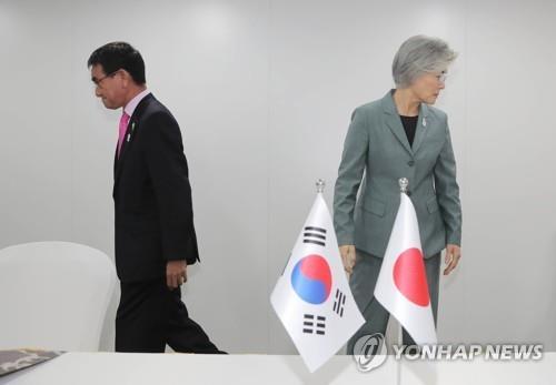资料图片:8月1日,在曼谷,韩国外长康京和(右)与日本外相河野太郎在举行会谈前握手后走向各自座位。这场韩日外长会无果而终。 韩联社