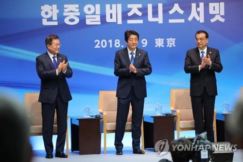 资料图片:2018年5月9日,在东京,文在寅(左)、安倍晋三(中)、李克强在韩中日工商峰会上起立鼓掌。 韩联社