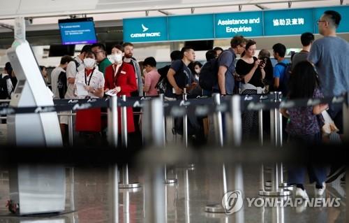 资料图片:8月13日,香港机场恢复运作,游客在办理登机手续。 韩联社/路透社