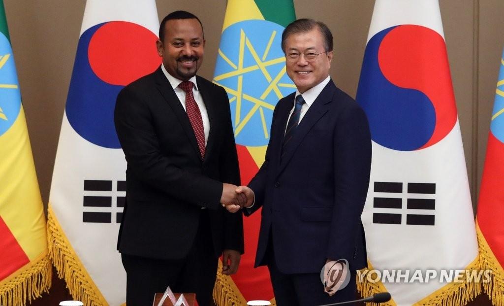 8月26日,在青瓦台,文在寅(右)与埃塞俄比亚总理阿比握手合影。 韩联社