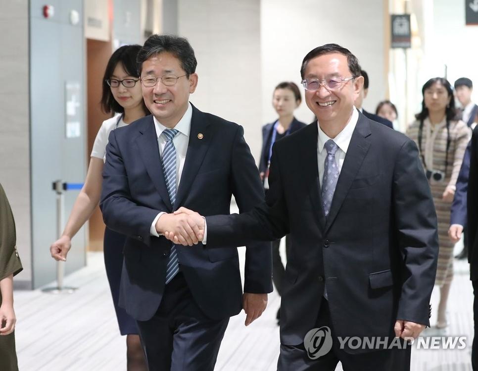 朴良雨(左)和雒树刚亲切握手。 韩联社