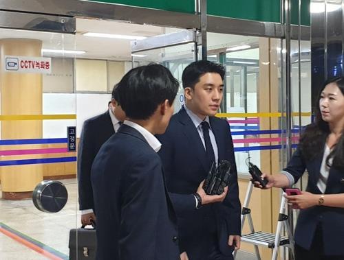 8月28日晚上,胜利(右二)在首尔地方警察厅智能犯罪侦查队接受调查后走出大楼。 韩联社