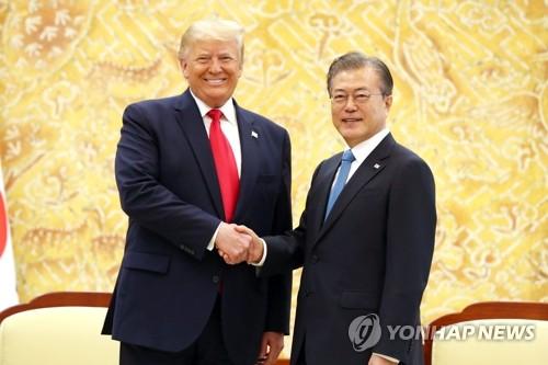 资料图片:6月30日,在青瓦台,韩国总统文在寅(右)与到访的美国总统特朗普握手合影。 韩联社