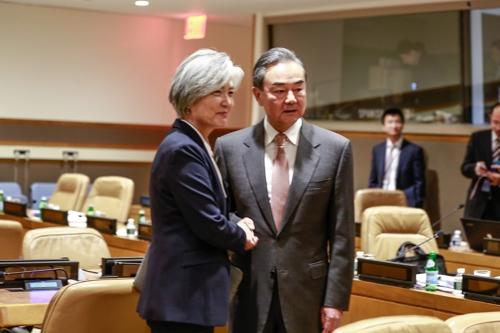 9月25日,在纽约,康京和(左)与王毅握手合影。 韩联社/韩国外交部供图(图片严禁转载复制)