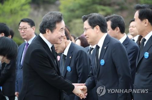 资料图片:4月19日,在首尔国立四一九民主公墓,李洛渊(左)与黄教安握手。 韩联社